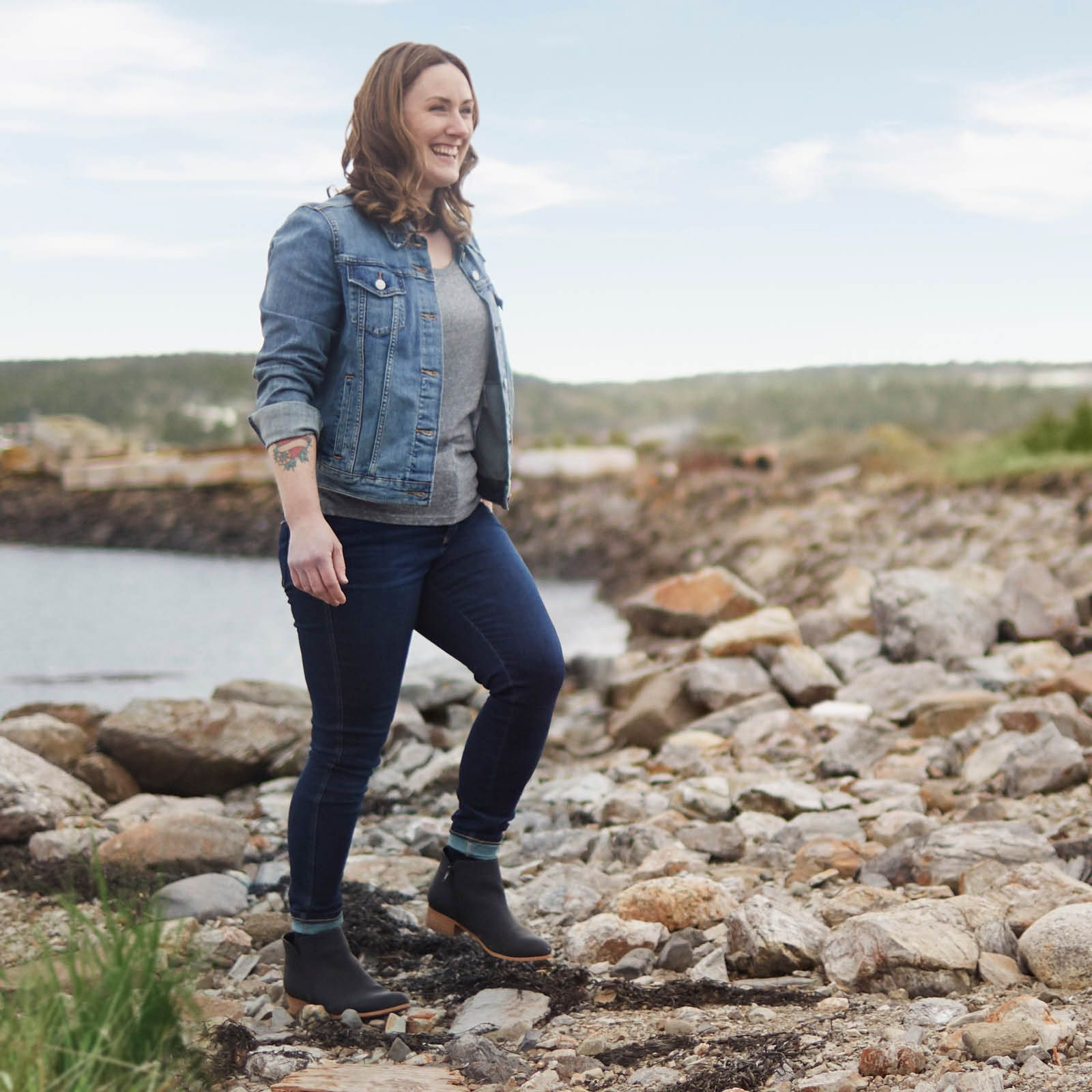 Jana Bookholt enjoying the water on a rocky beach.