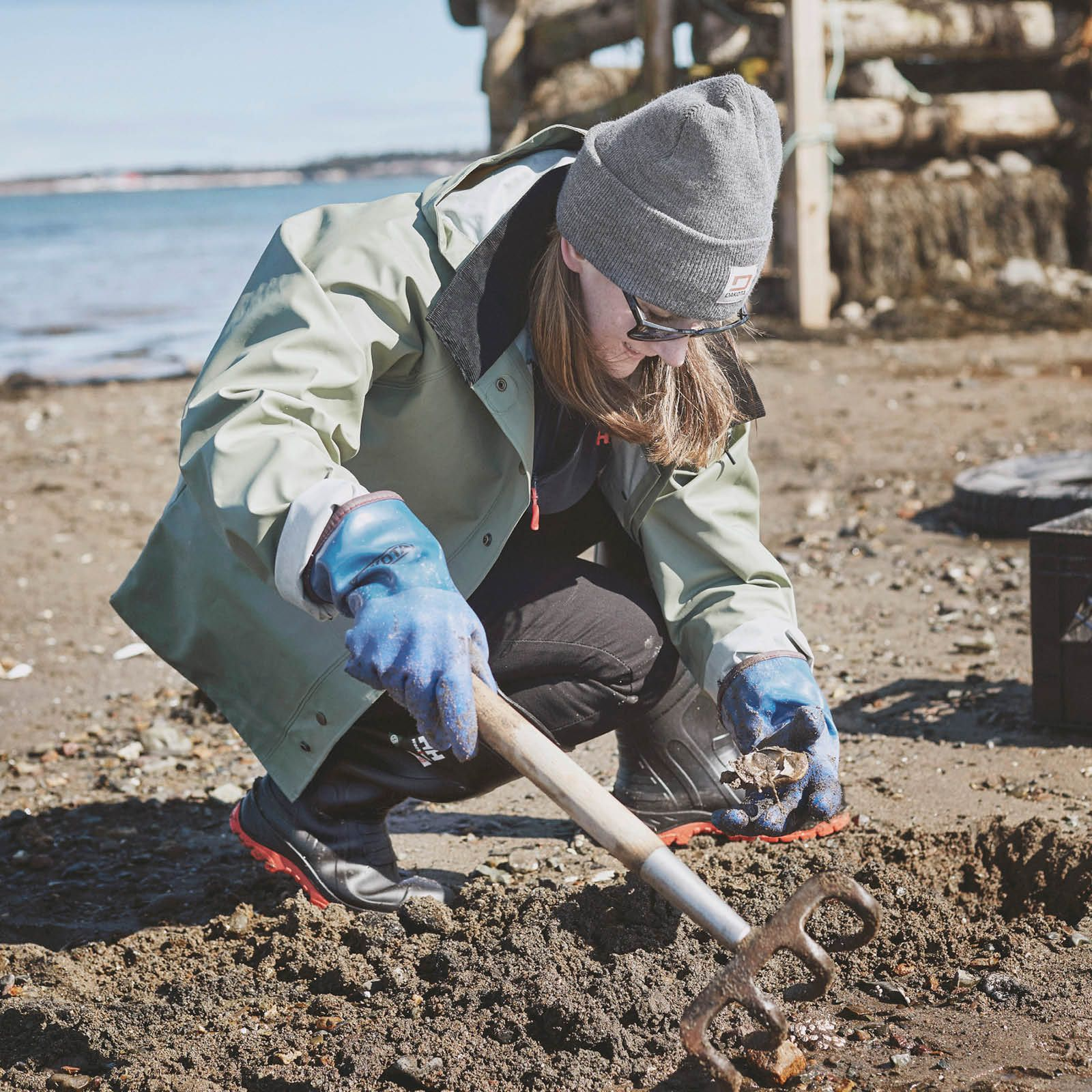 Jana Bookholt digging for clams on a beach.