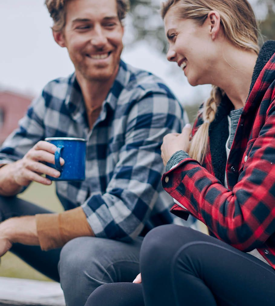 Couple enjoying coffee in their cozy, flannel shirts.
